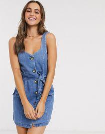 ASOS DESIGN denim button pinafore mini dress in blue at Asos
